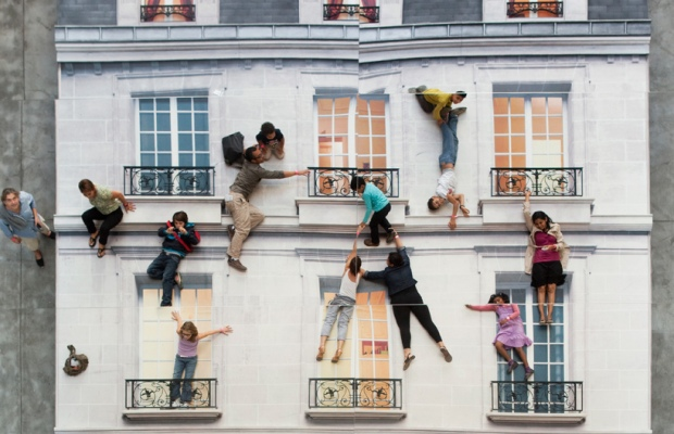 'Bâtiment' by Argentinian artist Leandro Erlich is a large-scale installation consisting of a mock-up building façade turned  on its side and a multi-storey mirror. Exhibiting as a part of Le Centquatre's group show 'In_Perception' in Paris, France, the piece allows visitors to view themselves in a gravity-defying illusion where they are hanging off the elevation of a four-level house. The work aims to challenge and skew the viewer's  comprehension of reality by using mundane elements of urban life that have slipped into the unconscious of the public. See more here - http://www.leandroerlich.com.ar/works.php